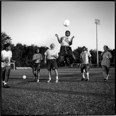 Photograph of The Queen Bees at Patriot's Point soccer team. Photograph depicts Kendra Coaxum heading a soccer ball.