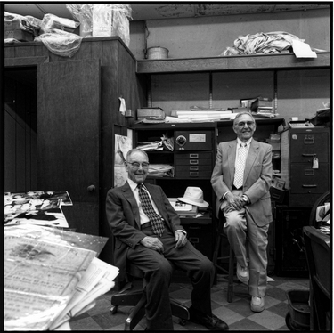 Photograph of Alwyn Goldstein and Philip Schneider in the back of Alwyn's store
