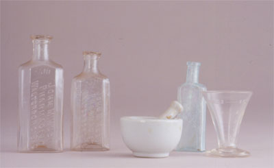 Apothecary bottles, mortar and pestle, and measuring cup from J. J. Klein drugstore (1845-1938)